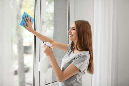 Foto de Beautiful woman cleaning window at home - Imagen libre de derechos