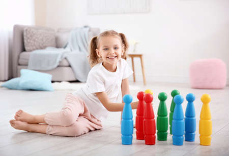 Photo pour Cute little girl playing with skittles at home - image libre de droit