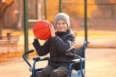 Foto de Little boy in wheelchair with ball on playground - Imagen libre de derechos
