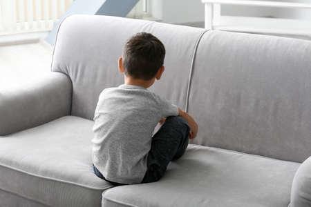 Foto de Little boy sitting on sofa at home. Child autism - Imagen libre de derechos