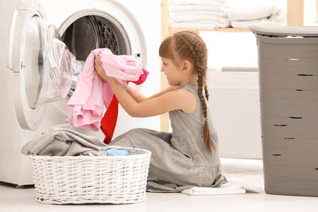 Foto de Cute little girl doing laundry indoors - Imagen libre de derechos