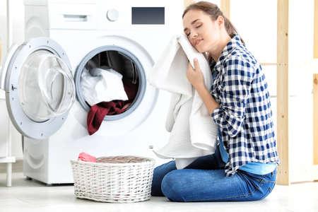 Photo pour Young woman doing laundry at home - image libre de droit