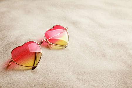 Photo pour Glasses in shape of heart on white sand - image libre de droit