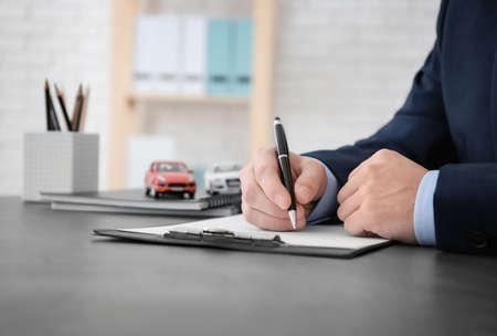Foto de Man filling in car insurance form at table - Imagen libre de derechos