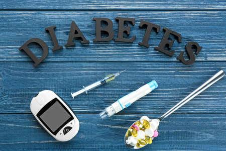 Photo pour Composition with word Diabetes, medicaments and digital glucometer on wooden background - image libre de droit
