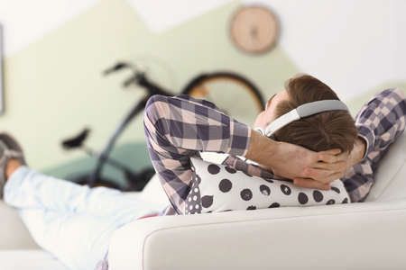 Photo pour Young man listening to music while relaxing on sofa at home - image libre de droit