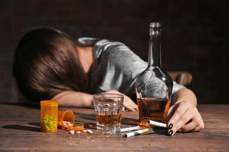 Photo pour Alcohol, drugs, cigarettes and unconscious woman on background - image libre de droit