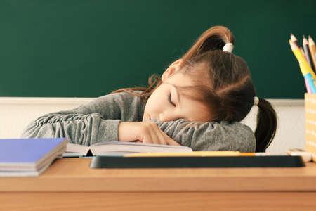 Foto de Sleeping little girl tired of doing homework in classroom - Imagen libre de derechos