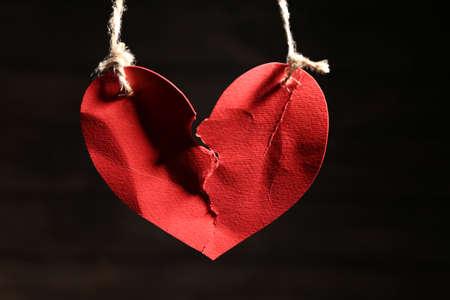 Foto de Ripped heart hanging on ropes against dark background. Relationship problems - Imagen libre de derechos