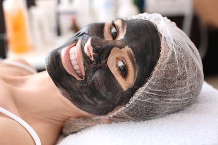 Photo pour Young woman with carbon nanogel on her face in salon. Peeling procedure - image libre de droit