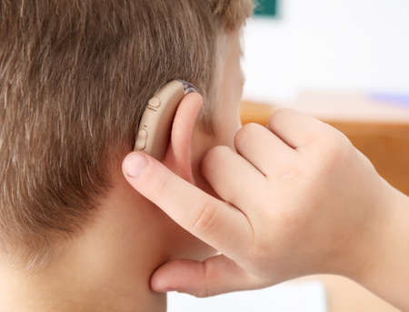 Foto de Little boy turning on hearing aid, closeup - Imagen libre de derechos