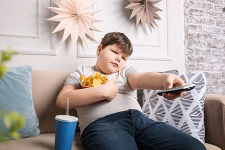 Photo pour Overweight boy watching TV with snacks indoors - image libre de droit