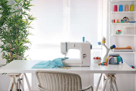 Photo pour Sewing machine with fabric on table in tailor workshop - image libre de droit