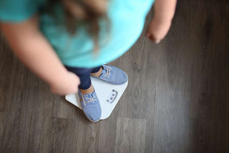 Photo for Overweight girl standing on floor scales indoors - Royalty Free Image
