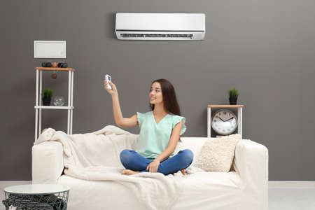 Photo pour Young woman switching on air conditioner while sitting on sofa at home - image libre de droit