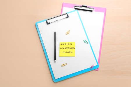 Foto de Clipboards and note with phrase Autism awareness month on light background - Imagen libre de derechos
