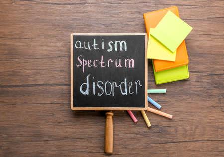 Foto de Chalkboard with phrase Autism spectrum disorder on wooden background - Imagen libre de derechos