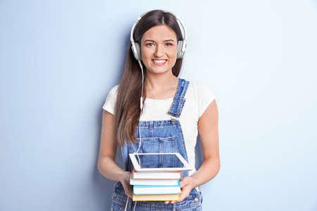 Photo pour Woman listening to audiobook through headphones on color background - image libre de droit