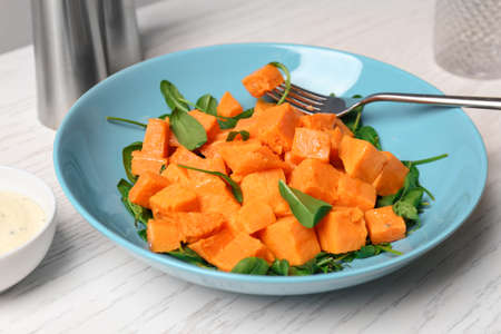 Photo for Plate with delicious cut sweet potato on table - Royalty Free Image