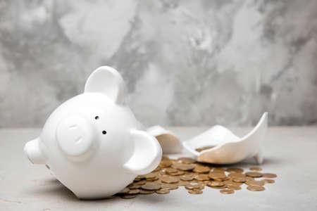 Foto de Broken piggy bank with money on table - Imagen libre de derechos