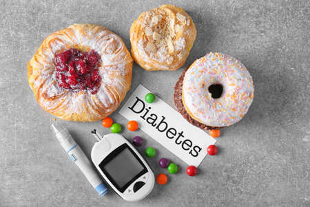 Foto per Digital glucometer, card with word Diabetes and sweets on table - Immagine Royalty Free