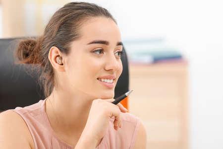 Foto de Young woman with hearing aid indoors - Imagen libre de derechos