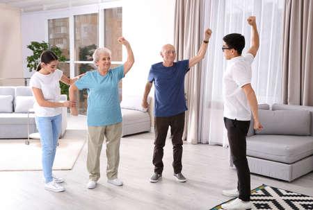 Foto de Senior people doing exercises with caregivers at home - Imagen libre de derechos