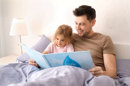 Photo pour Father with little daughter reading bedtime story at home - image libre de droit