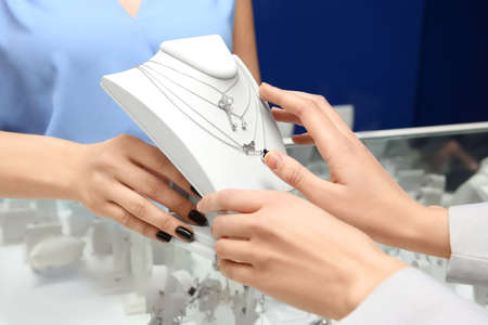 Foto de Young shop assistant helping woman choose necklace in jewelry store - Imagen libre de derechos