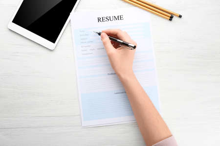 Foto de Woman filling in resume form at table. Job interview concept - Imagen libre de derechos