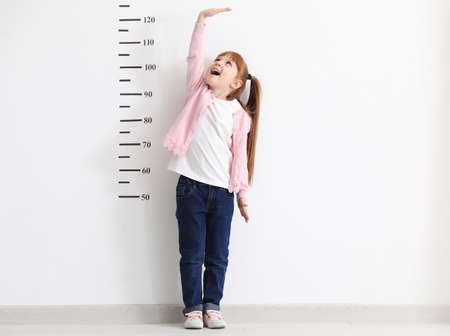 Foto per Little girl measuring height near white wall - Immagine Royalty Free