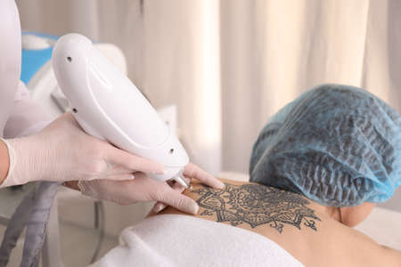 Photo pour Cosmetologist with patient and professional tattoo removal laser in salon - image libre de droit