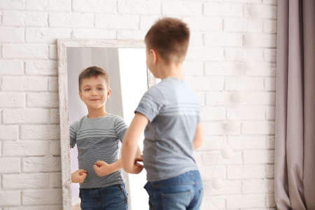 Photo pour Cute little boy posing in front of mirror indoors - image libre de droit
