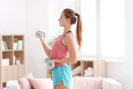 Photo for Beautiful young woman doing fitness exercise with dumbbells at home - Royalty Free Image