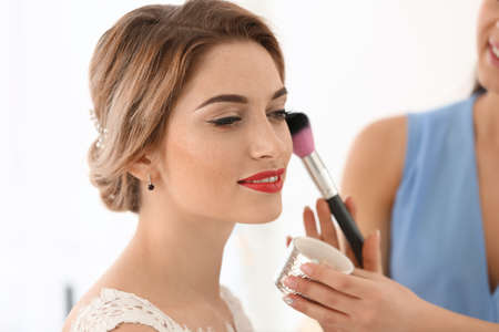 Foto de Makeup artist preparing bride before her wedding - Imagen libre de derechos