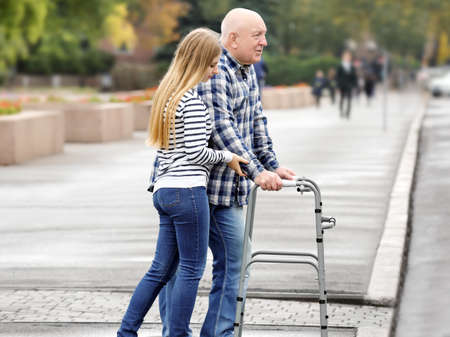 Photo pour Young woman helping elderly man with walking frame to cross the road - image libre de droit