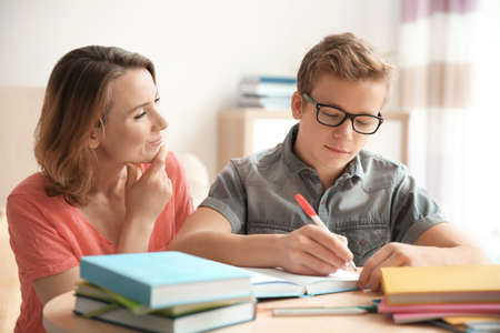 Foto de Teenager with mother doing homework at home - Imagen libre de derechos