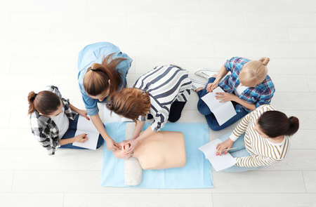 Foto de Group of people practicing CPR on mannequin at first aid class - Imagen libre de derechos
