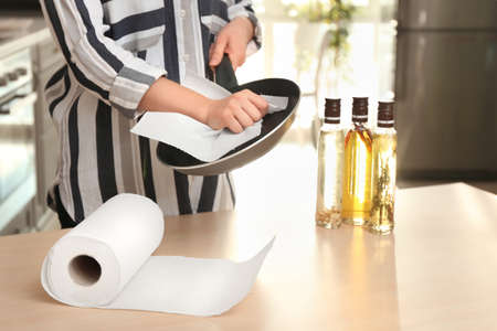 Photo for Woman wiping frying pan with paper towel indoors - Royalty Free Image