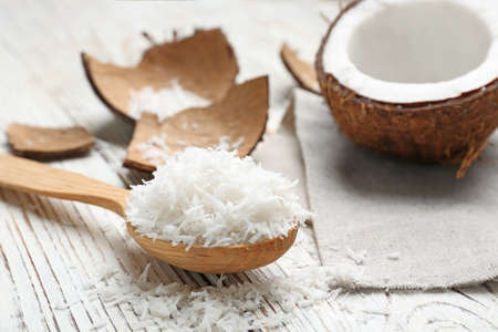 Photo for Wooden spoon with fresh coconut flakes on wooden background - Royalty Free Image