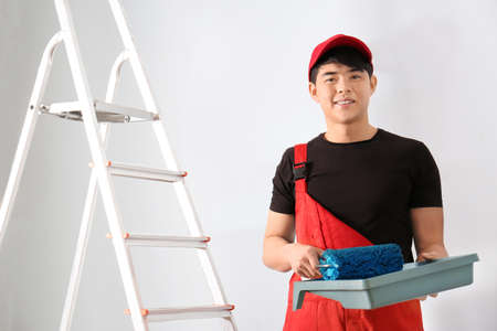 Photo for Male decorator with paint and roller indoors - Royalty Free Image