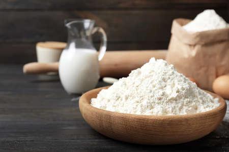 Photo pour Bowl with flour on wooden table - image libre de droit