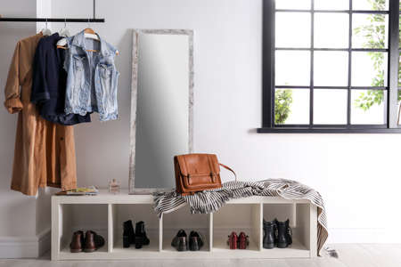 Photo for Modern hallway interior with hanging clothes and shoe rack - Royalty Free Image