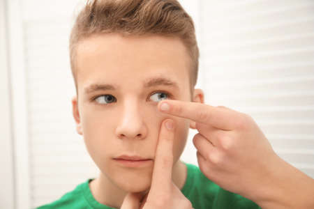 Photo for Teenage boy putting contact lens in his eye indoors - Royalty Free Image