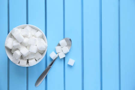 Photo for Bowl with refined sugar cubes on color wooden background, top view - Royalty Free Image