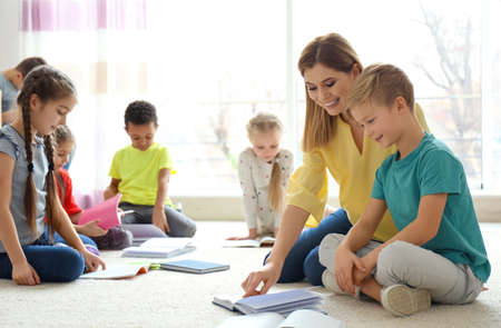 Photo for Female teacher helping boy with his homework in classroom at school - Royalty Free Image