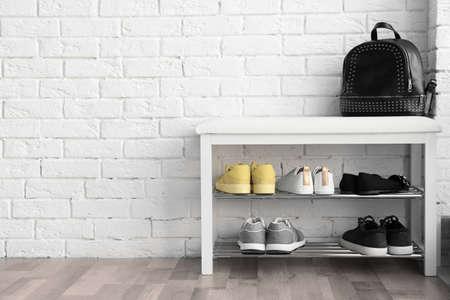 Foto de Collection of stylish shoes on rack storage near white brick wall - Imagen libre de derechos
