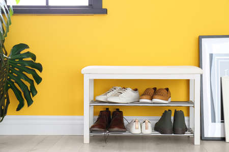 Foto für Collection of stylish shoes on rack storage near color wall in room - Lizenzfreies Bild