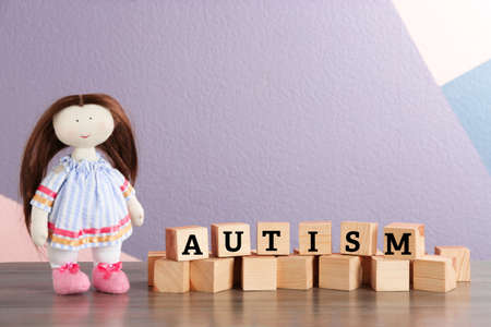 Foto de Doll and cubes with word Autism on table - Imagen libre de derechos
