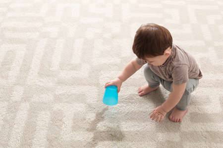 Photo pour Baby sitting on carpet with empty glass - image libre de droit